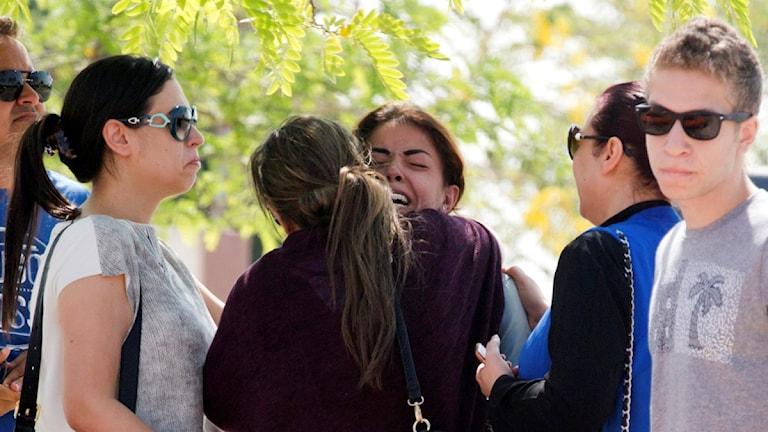 Alla ser ledsna ut. En gråtande kvinna får en kram.