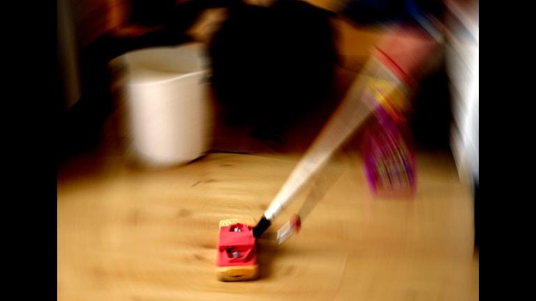 Någon städar golvet genom att torka med en mopp.