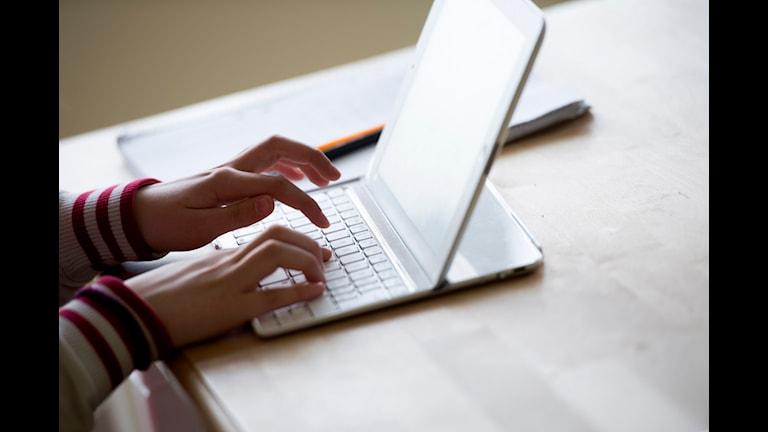 På bilden syns två händer som skriver på en dator.