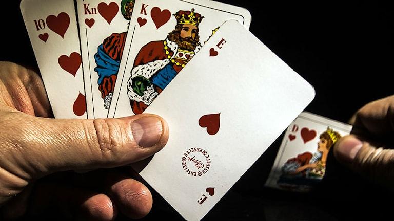 En hand håller upp några kort.