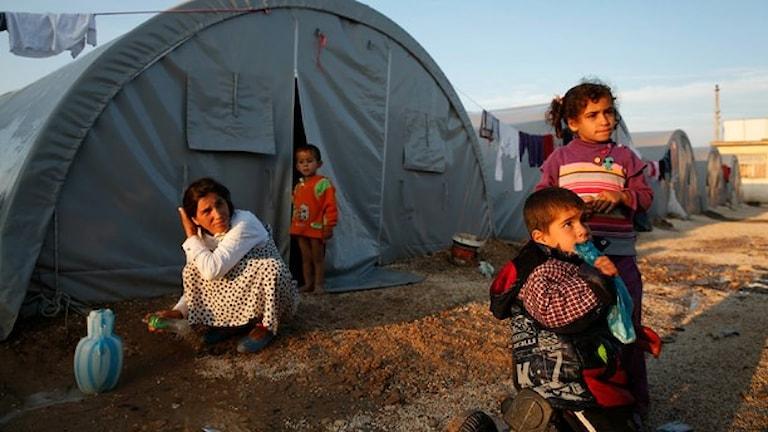 Några barn leker utanför ett tält.