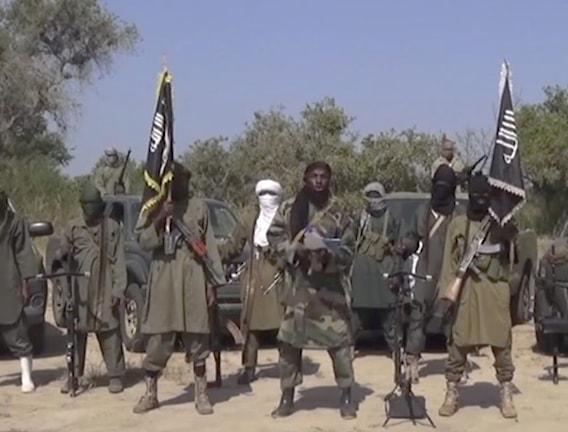 De har vapen och är klädda i gröna kläder. De har också två flaggor där det är skrivet något med arabiska bokstäver.