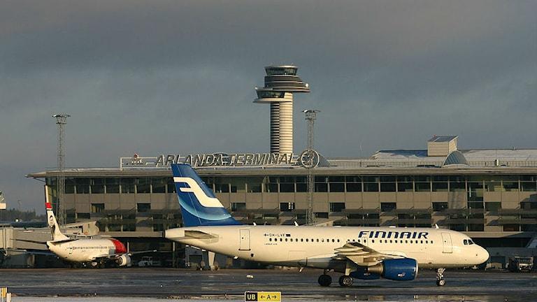 På bilden syns två flygplan nere på marken och ett högt torn.
