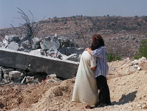 Två palestinska kvinnor tröstar varandra utanför resterna av ett rivet hus.