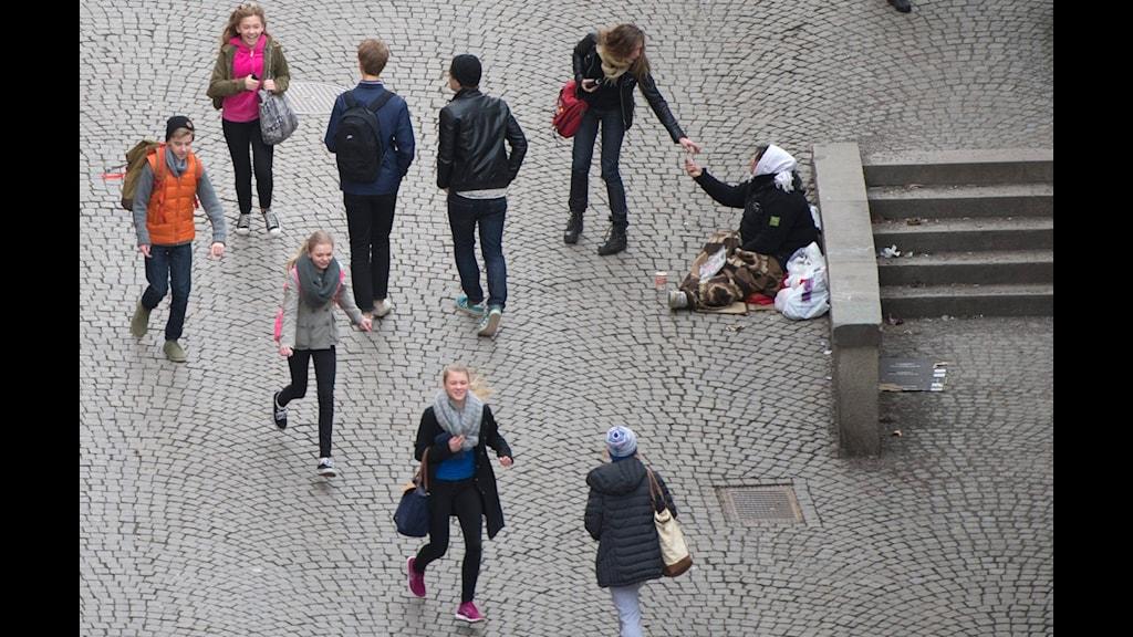 En tiggare får något av en kvinna som går förbi på gatan.