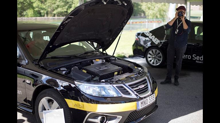 Bilen är svart. Det står på den att det är en elbil.