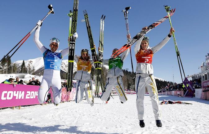 fyra glada skidåkare som hoppar av glädje i luften
