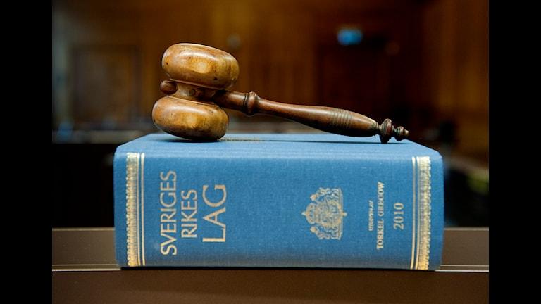 Lagboken är blå och texten står med gyllenebokstäver. Ovanpå ligger en klubba av trä.