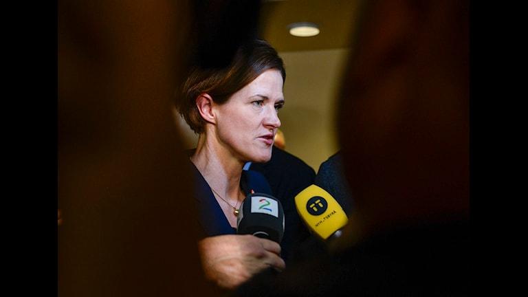 bilden visar en kvinna omgiven av journalister