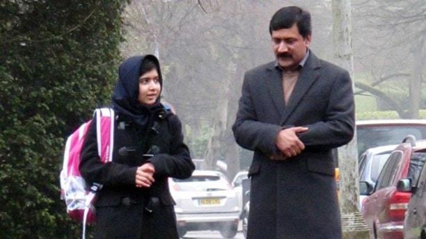 En flicka med ryggsäck bredvid sin pappa