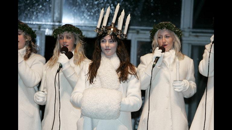 Lucia är klädd i vitt och hör en krona med ljus på huvudet.