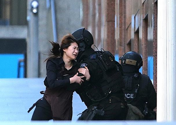 En kvinna kommer springande. Håret fladdrar. Hon kastar sig i armarna på en polis.