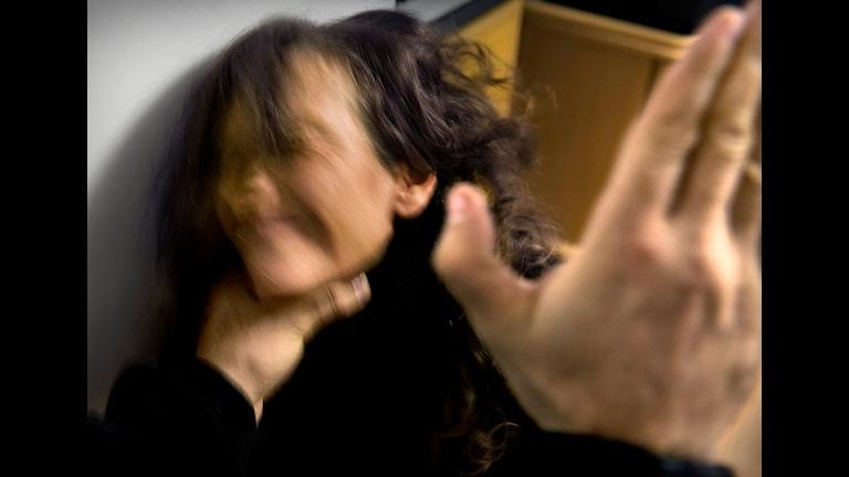 En man slår en kvinna. Bilden är suddig så det syns inte vilka personer det är.