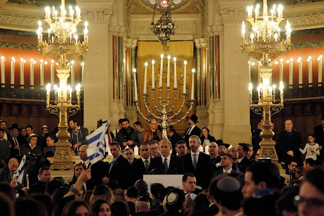Männen har en kalott på huvidet och det brinner många levande ljus i synagogan.