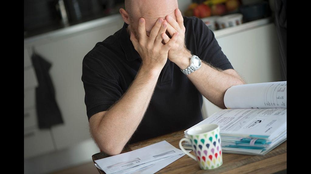 En skuldsatt man sitter vid köksbordet omgiven av obetalda räkningar.