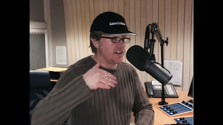 Mattias har en keps på huvudet. Där står det Lasse Stefanz. Han gör en gest med handen.