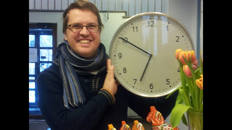 Mattias håller upp en stor klocka som visar tiden 18:50.