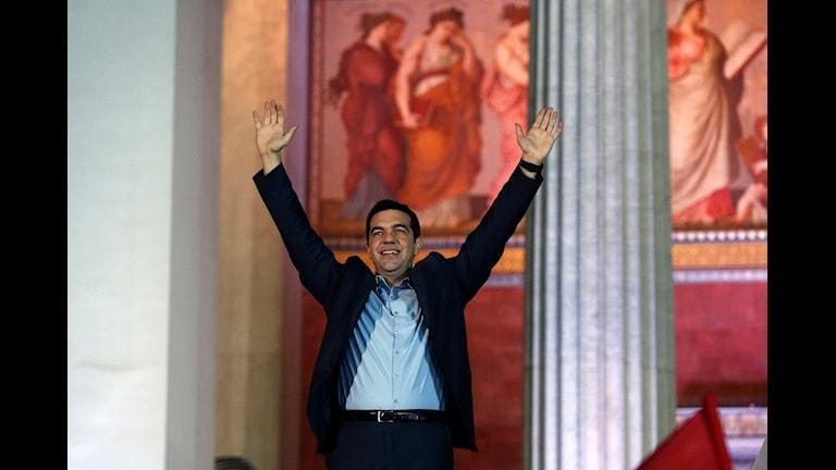 Han håller upp båda armarna i luften och ser glad ut.