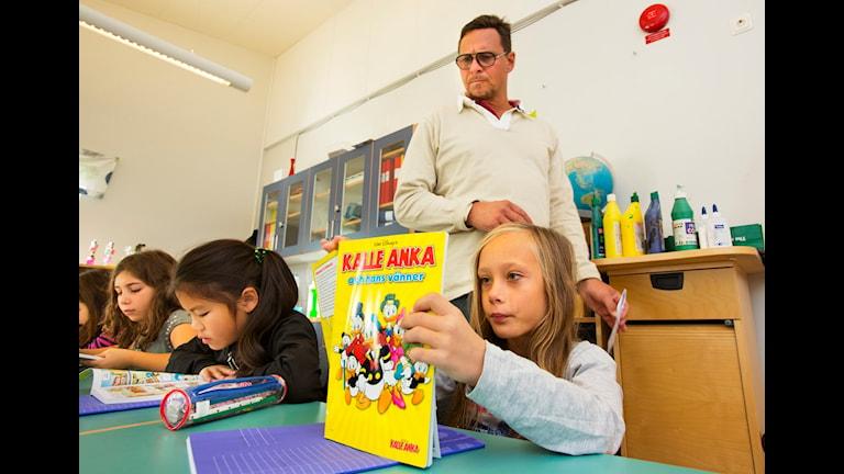 Barnen läser serietidningar i klassrummet.