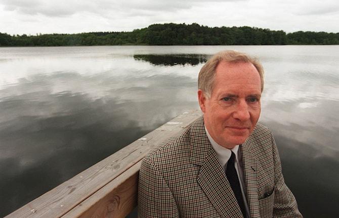 Han sitter på en brygga vid vattnet. Han är klädd i kostym.