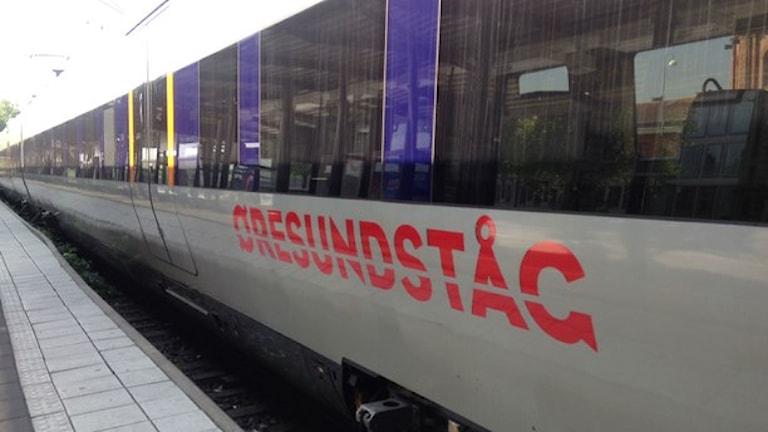 """Tåget står vid en perrong. På tåget står texten: """"Öresundståg""""."""