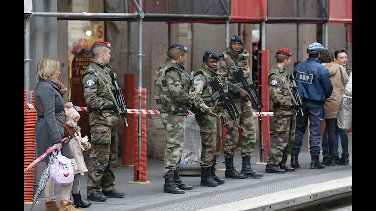 Vakter med vapen står utanför huset.