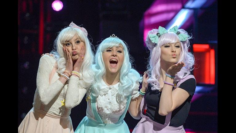 Tre tjejer i färgglada kläder med blått och rosa hår