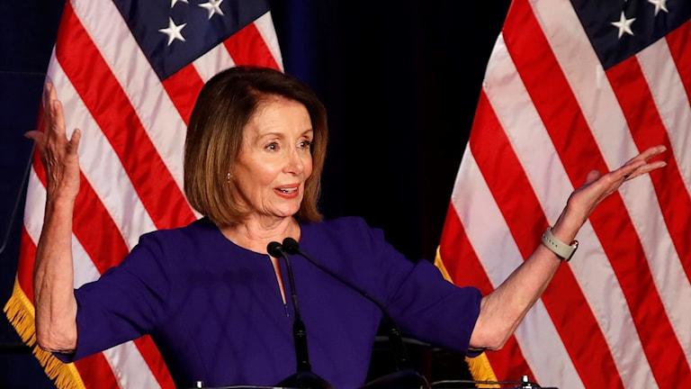 På fotot ser man att Nancy Pelosi är glad. Bakom henne hänger amerikanska flaggor.