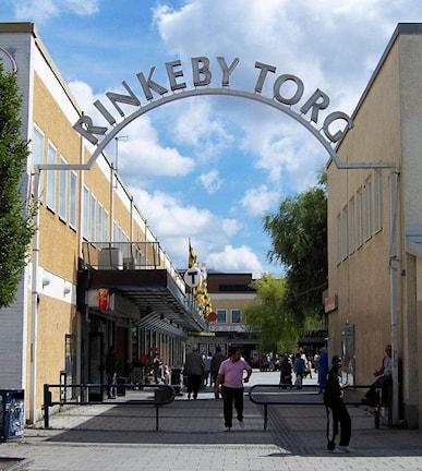"Det går en stor båge över gatan. På den skylten står det ""Rinkeby Torg""."