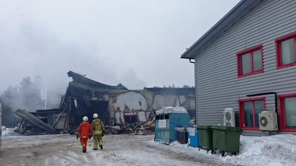 Rök från en brinnande hus och två brandmän