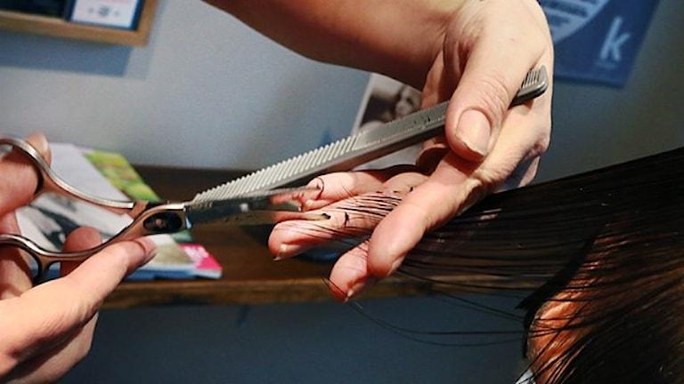 Det är en närbild på en hand som klipper hår.