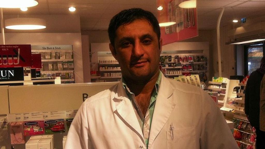 En man från Syrien i en vit apoteksrock