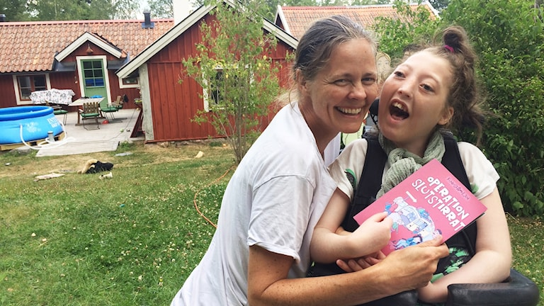 Bilden visar en mamma med hennes dotter i rullstol.