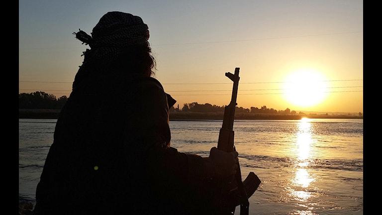 En IS-krigare sitter och vilar sig vid floden Eufrat i Irak. Solen går ner och glimmar i vattnet.