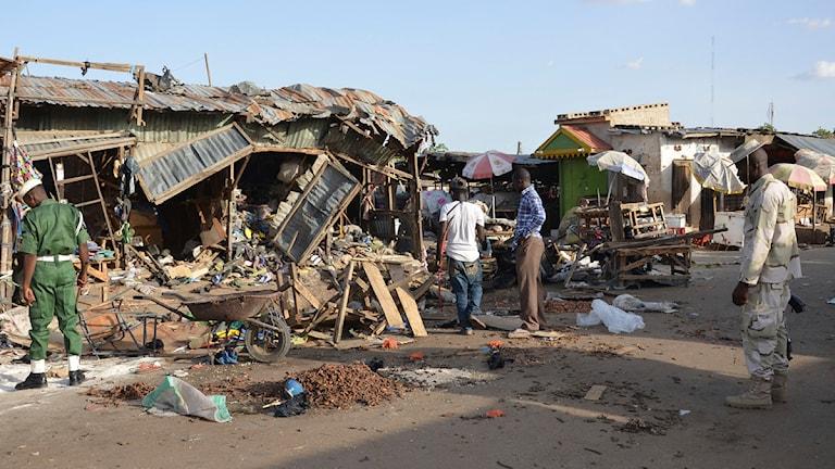 Några människor tittar på hus vid en marknad i Nigeria som förstördes i juni