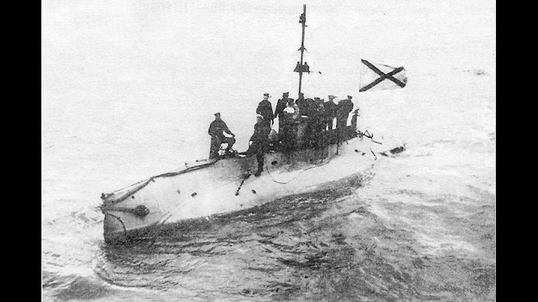 Det är en ganska liten ubåt. Den har gått upp till vattenytan och några soldater står uppe på båten.