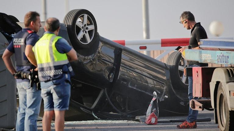 """Det är en svart personbil av märket Audi. Den ligger upp och ner och på gatan finns krossat glas. Några personer står bredvid bilen. En av dem har en väst på sig med texten """"polis"""" och han har en pistol på sig."""