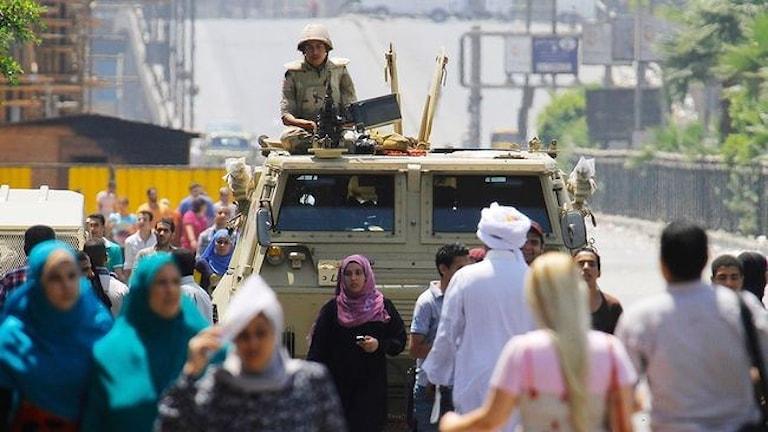 En militär i Egypten i en bil och människor framför den.