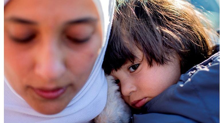 Hon har muslimsk huvudduk. Hon håller i ett barn. Båda ser trötta och ledsna ut.