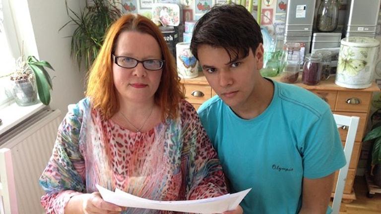 En kvinna i rött hår och glasögon och hennes son i kort mörkt hår och en blå tröja.