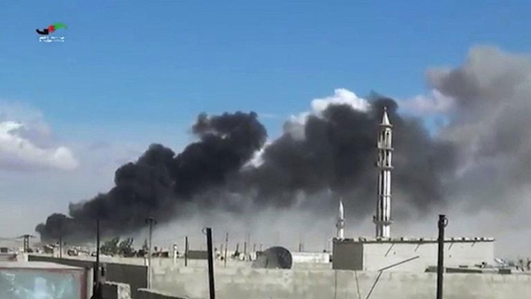 Svart rök stiger upp bakom en moské.
