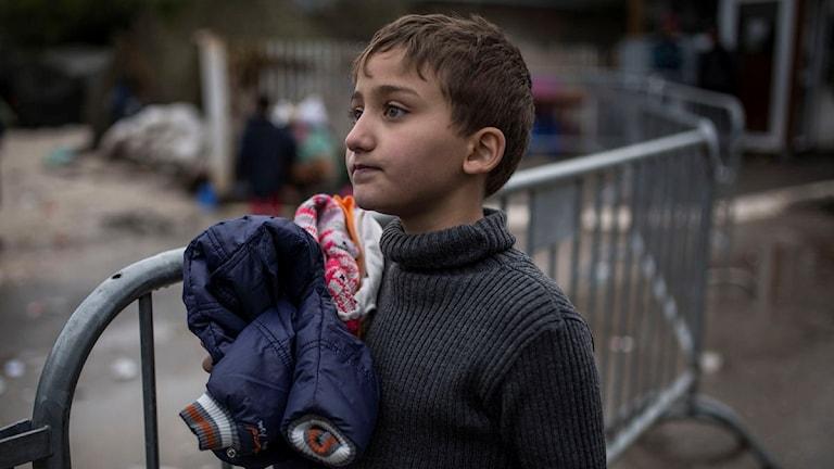 Han står vid ett staket och håller barnkläder några barnkläder.