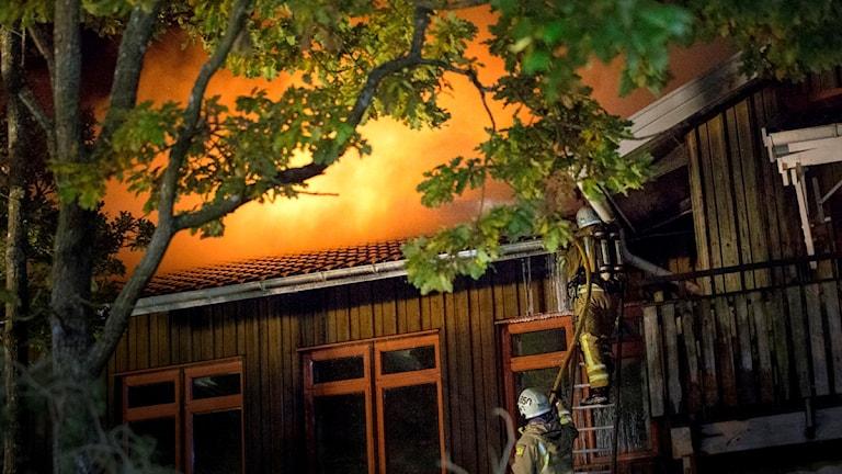 Det är ett grönt hus av trä. Eldslågor stiger upp ur taket.