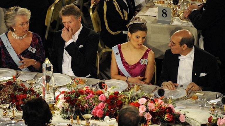 Det är mycket blommor på bordet. Männen är klädda i frack och kvinnorna har klänning.