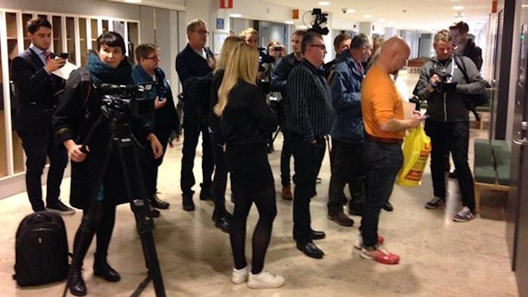 En del journalister har kamera med sig. De väntar vid en stängd dörr.