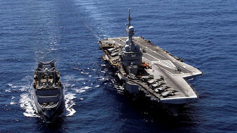 Ovanpå hangarfartyget är stridsflygplan parkerade.