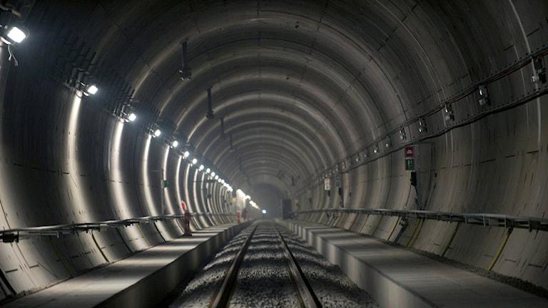 Det är en rund tunnel. Genom tunneln går ett spår för tåg.