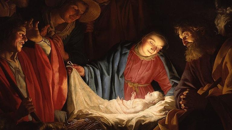 Det strålar ljus från Jesusbarnet. De vuxna står bredvid och tittar på honom.