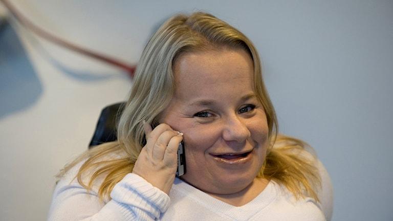 Hon pratar i telefon.