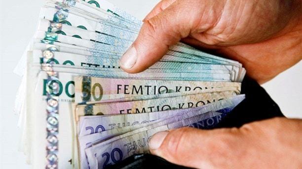 En bunt med pengar i en hand.